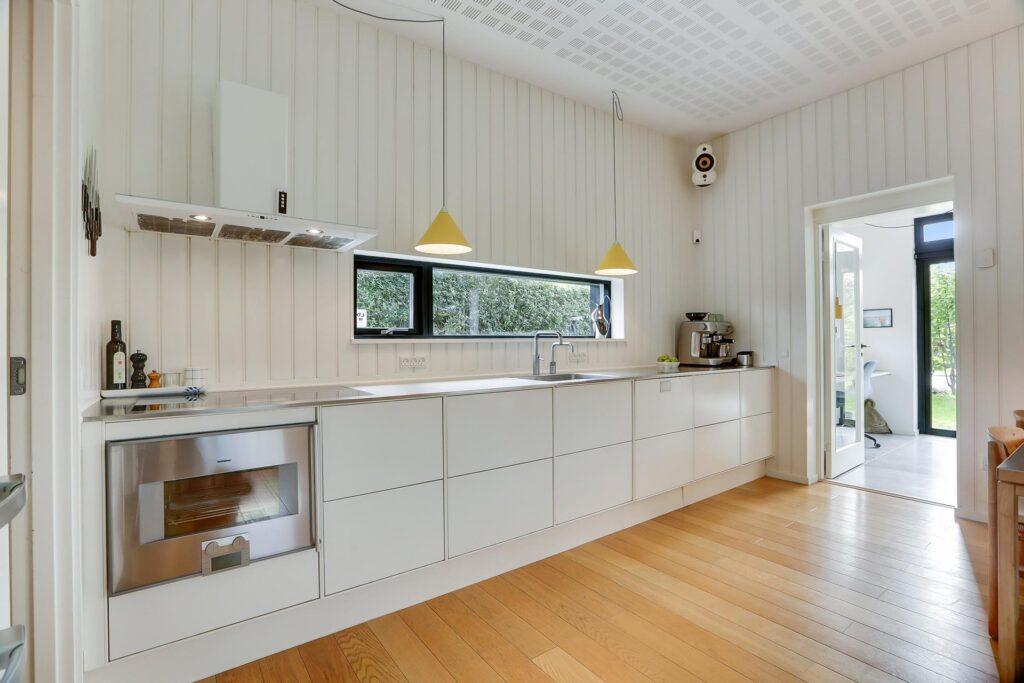 Lækkert lyst køkken med hvide panelvægge.