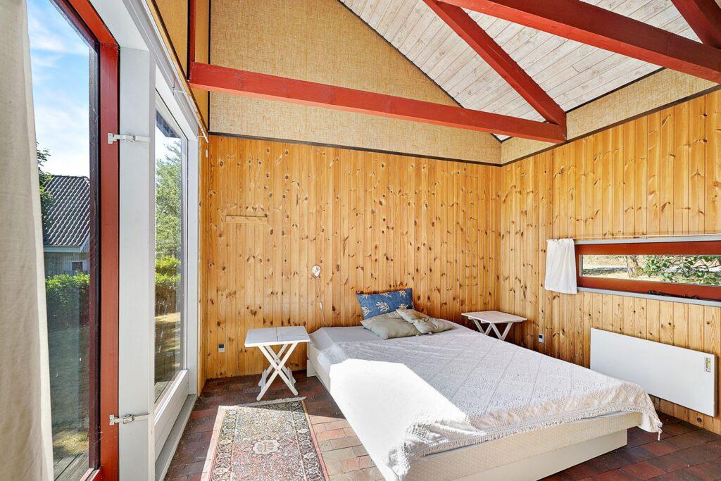 Soveværelse i sommerhus med træbeklædning