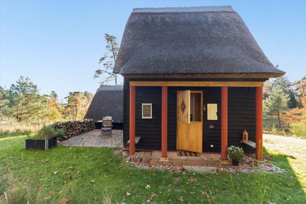Sommerhus i Tibirke Bakker, Sortmalet træhus med stråtag, Arkitekttegnet hus til salg