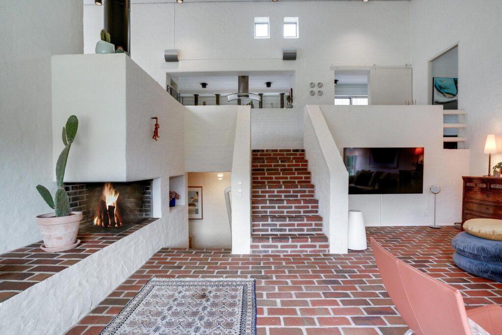 Højloftet stue med pejs, brutalisme