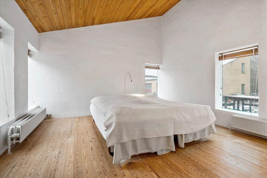 Rustikt arkitekttegnet hus fra 1980, teglstensgulv, vandskurede hvide vægge og trælofter