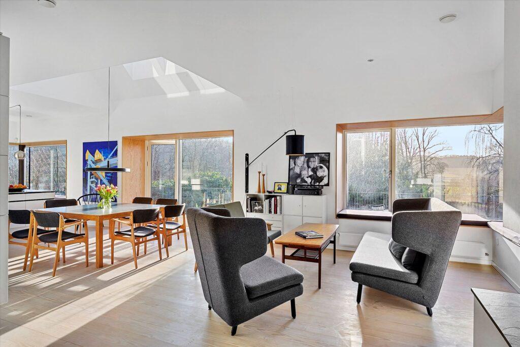 Stue med ovenlys, dybe vinduesnicher foret med træ.
